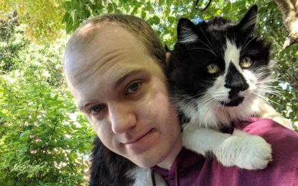 Balck and white cat sits on shoulder